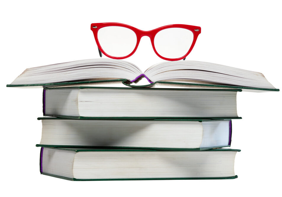 red glasses on open book, pile or stack of books isolated over white background